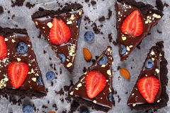 Close-up of slices no bake cake. Close-up of slices no bake Chocolate cake tart with fresh blueberries, strawberries, decorated with finely chopped almonds on Stock Image
