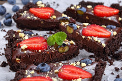 Close-up of slices of no bake cake. Close-up of slices no bake Chocolate cake tart with fresh blueberries, strawberries, decorated with mint leaves, and finely Stock Photo