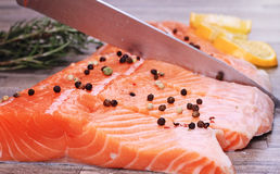 Close up on slicing raw salmon with sharp knife Royalty Free Stock Photo