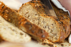 Close up of Slicing Wholemeal Seeded Bread Loaf. Close up macro shot of a person using a knife to slice a wholemeal rustic seeded brown bread Royalty Free Stock Photo