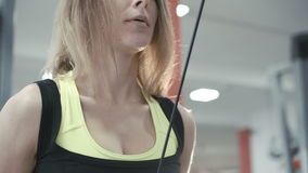Close up of slim girl workout with gym simulator for muscles in the gym in 4K stock video footage