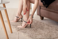 Close up of slim legs of woman wearing high heel shoes. Close up of slim legs of woman wearing high heel beige shoes. Red manicure royalty free stock photography