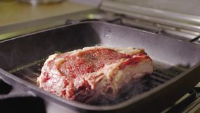 Unrecognizable man chef hand puts a raw red beef steak on a black hot grill pan, close up view slow motion video in 4K. Close up slo motion video of an stock images