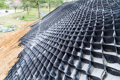 Close up on slope erosion control grids on steep slope. Royalty Free Stock Photo