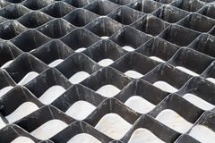 Close up on slope erosion control grids on steep slope. Stock Photos