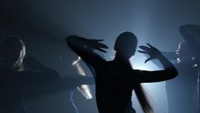 Close-up. Slow motion of ballerinas silhouettes dancing elements of ballet. Close-up. Slow motion of ballerinas silhouettes in light dresses dancing elements of stock video footage