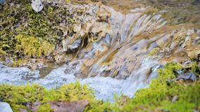 Close-up slow motion cascade stream surrounded by green and petrified moss. High mineral content in mountain water.  stock video footage