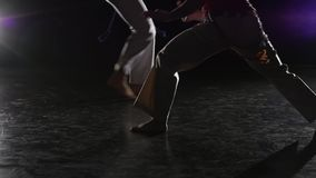 Beautiful women practicing capoeira in darkness against spotlight in studio. Close-up slow motion. Close-up slow motion. Couple of beautiful women are practicing stock footage