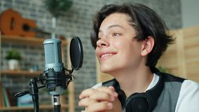 Close-up slow motion of happy teenager blogger speaking in microphone at home. Recording audio smiling enjoying activity. Youth culture and lifestyle concept stock footage