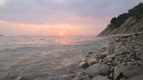 Close-up slow motion low wide angle small sea waves rolling on a rocky beach. Movement along the beach forward. Seaside. Evening sunset on a pebble rocky beach stock footage