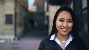 Close-up slow motion portrait of attractive Asian girl looking at camera with happy smile standing in the street wearing. Trendy clothing leather jacket and stock footage