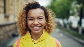 Close-up slow motion portrait of attractive mixed race girl looking at camera with happy smile expressing positive