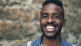 Close-up slow motion portrait of African American male with expressive face smiling showing teeth and looking at camera