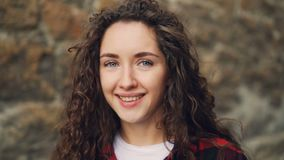 Close-up slow motion portrait of pretty girl brunette with curly hair looking at camera with serious face then smiling