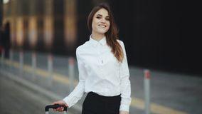 Stylish successful woman with suitcase waiting for taxi. Close up, slow motion. Portrait of woman in a white shirt near the hotel waiting for a taxi. Attractive stock video footage