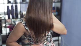 A close-up slow-motion shot of a girl in a beauty salon admires her long straight shiny hair after keratin straightening. The concept of hair care in the salon stock video