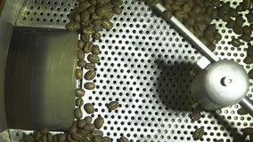 Close up slow motion shot of raw roasted coffee beans drying in factory machine, coffee production stock video
