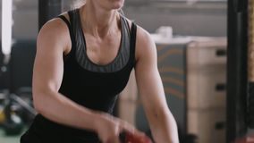Close-up slow motion, young beautiful athletic blonde woman working out exercising with battle rope in large gym. Determination, fitness and following healthy stock footage