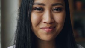 Close-up slowmotion portrait of charming Asian girl with dark eyes, perfect skin with make-up and white teeth looking at. Close-up slowmotion portrait of stock video footage