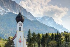 Small Bavarian church and snowy Zugspitze peak in springtime. Close-up of small Bavarian domed village church with white facade and clock tower with snowy royalty free stock photo