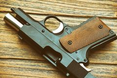 Close-up of small black gun compact handgun lying on wooden. Stock Images