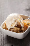 Close up of small bowl of freshly served peach crisp Royalty Free Stock Images