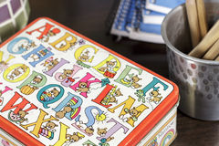 Close-up of small box decorated with drawings for childhood vocabulary learning. A small metal box decorated with drawings of teddy bears with diverse objects or Stock Image