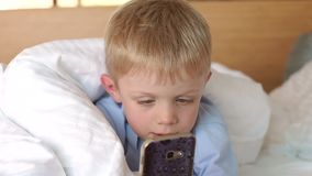 Close-up of a small boy lying on the bed under a warm white blanket with a phone. In his hands. Slow motion stock video