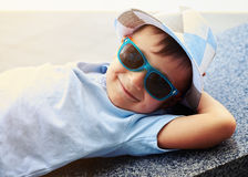 Close-up of small boy in sunglasses lying with hands under his h Stock Photo