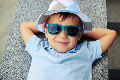 Close-up of small boy in sunglasses lying with hands under his h Royalty Free Stock Photography