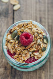 Close-up of Small Breakfast Pot filled with Granola and topped with Fresh Raspberry. Overhead, close-up view of breakfast pot filled with homemade granola and Royalty Free Stock Photography