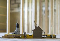 Close-up of small brown model house and building tools on wooden Royalty Free Stock Image