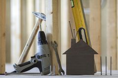 Close-up of small brown model house and building tools on wooden royalty free stock images