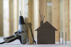 Close-up of small brown model house and building tools on wooden. Planks in unfinished room under construction background. Investments in real estate, property Stock Photo
