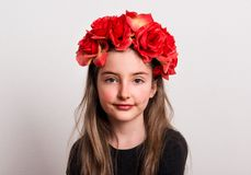 A close-up of small girl with flower headband sitting in a studio. Royalty Free Stock Images