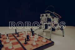 Close Up. A Small Gray Robot Is Playing Chess. Empty Room. Workshop Background. Innovation Technology. Artifical Intelligence. Technical Industry. Four Limbs stock photos