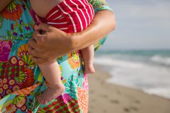 Close up of a small newborn baby on the hands of his mom. Sunny day on the ocean beach as a background. Outdoors. Bright dress and stock images