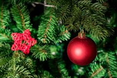 Close up red bauble on artrificial Christmas tree stock photo
