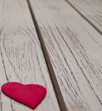 A single red heart on a wooden table. A close up of a small red heart laying on a white wooden table Royalty Free Stock Images