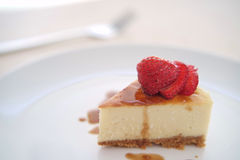Close up of small slice of cheesecake on a big plate Royalty Free Stock Photos