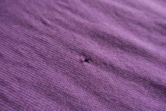 Closeup of small tear in pink knitted fabric. Close up of small tear in pink knitted fabric stock photos