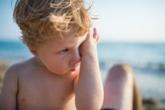 A close-up of small toddler boy on beach on summer holiday. Copy space. A close-up of small blond toddler boy on beach on summer holiday. Copy space stock photos