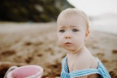 A close-up of small toddler girl on beach on summer holiday, playing. royalty free stock images