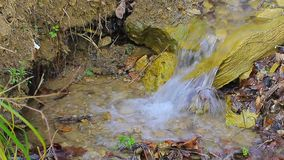 The close up of small waterfall creek making water bubbles. The close up of small waterfall creek with water splashing on the stones making water bubbles stock video footage