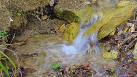 The close up of small waterfall creek making water bubbles. The close up of small waterfall creek with water splashing on the stones making water bubbles stock footage