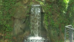 Close-up of a small waterfall in a deep forest on sunny day. Close-up of a small waterfall in a deep forest stock footage
