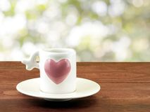 Close-up small white coffee cup with big pink heart on white ceramic saucer and dark brown wooden table top with light bokeh from. Space between green leaf Stock Photography