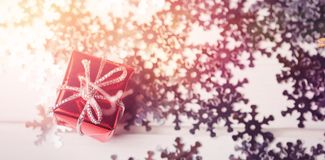 Small wrapped gift box and snowflake scattered on wooden table Stock Photos