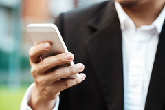 Close-up smart Business man wearing modern black suit and white. Shirt and texting on mobile smart phone Royalty Free Stock Image