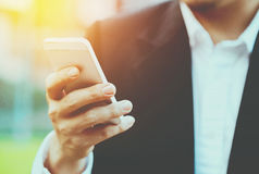 Close-up smart Business man wearing modern black suit and white. Shirt and texting on mobile smart phone with flare light Stock Photos